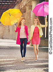 Two girlfriends walking during windy day - Two cheerful...