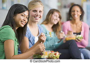Teenage girls enjoying healthy lunches together