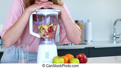 Pretty woman leaning on her juicer at home in the kitchen