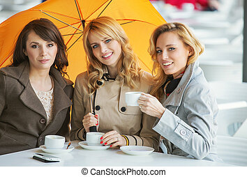 Three women, the coffee and the umbrella - Three pretty...