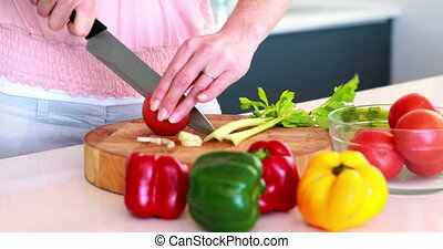Woman slicing tomato on a chopping - Woman slicing tomato on...