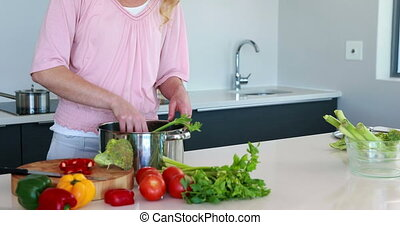 Smiling woman putting vegetables into a saucepan at home in...