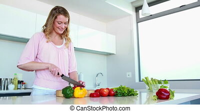 Smiling woman slicing vegetables on