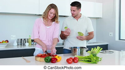 Smiling couple preparing a healthy dinner together at home...