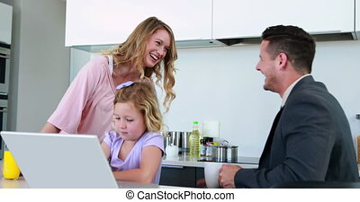 Mother and father laughing together while daughter uses...
