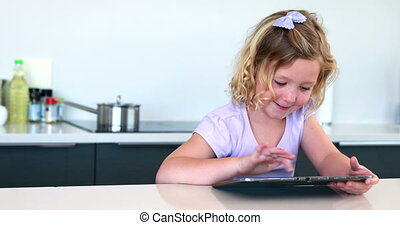 Little girl using a digital tablet at home in the kitchen