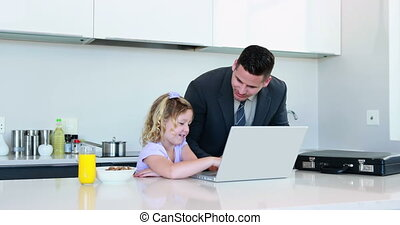 Father using the laptop with his daughter before work at...
