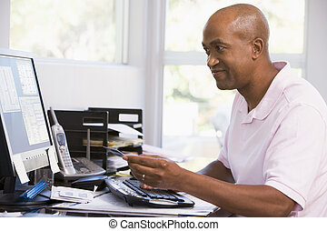 Man in home office using computer holding credit card and...