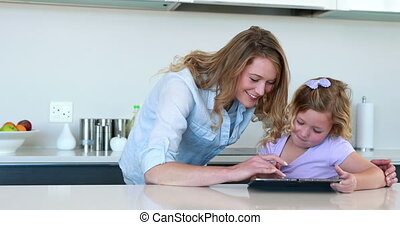 Little girl using a digital tablet with her mother at home...