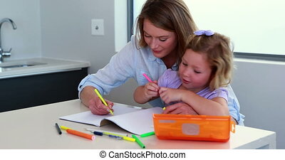 Mother and daughter drawing at the table at home in the...