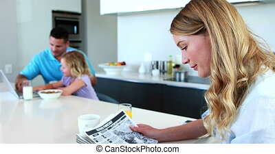 Mother reading the paper while fami - Mother reading the...