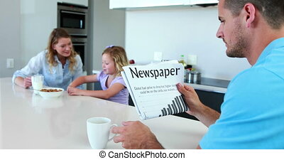 Father reading the newspaper while family has breakfast at...