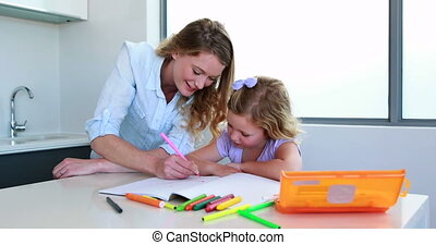 Smiling mother and daughter drawing at the table at home in...
