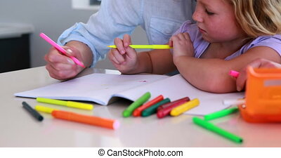 Pretty mother and daughter drawing at the table at home in...
