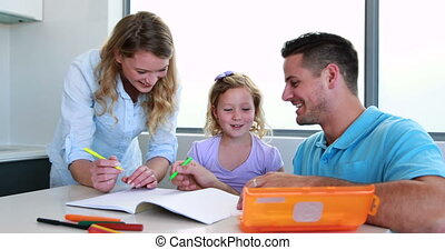 Smiling parents and daughter drawing at the table at home in...