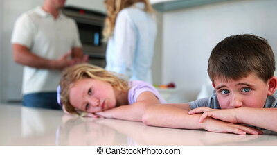 Young siblings blocking out noise from parents fighting at...