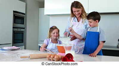 Happy mother and children making a cake together at home in...