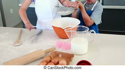 Smiling siblings making a cake together at home in the...