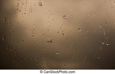 Rain drops on window across clouds - Rain drops on window...