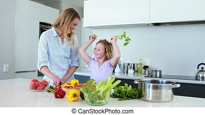 Smiling mother and daughter preparing a healthy dinner...