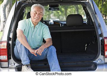Man sitting in back of van smiling