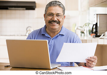 Man in kitchen with laptop and paperwork smiling