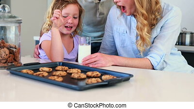 Little girl having milk and cookies with her parents at home...