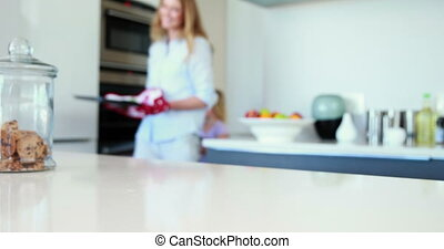 Mother taking hot cookies from oven