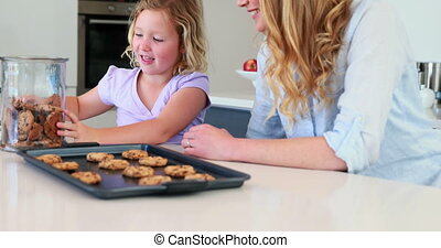 Little girl having milk and cookies with her mother at home...