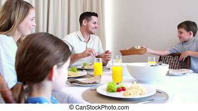 Happy young family at the dinner table at home in the...