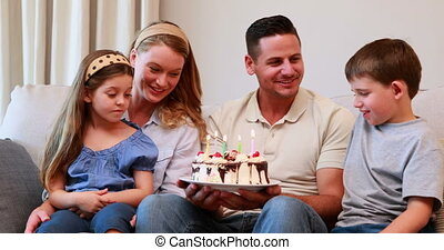 Happy young family sitting on sofa celebrating a birthday at...