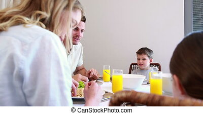Happy young family talking at the dinner table at home in...