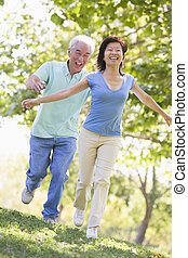 Couple running outdoors in park by lake smiling