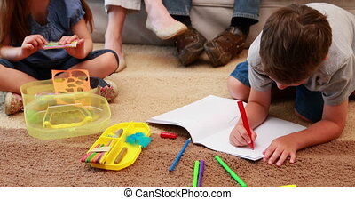 Young siblings doing arts and crafts on the rug while...