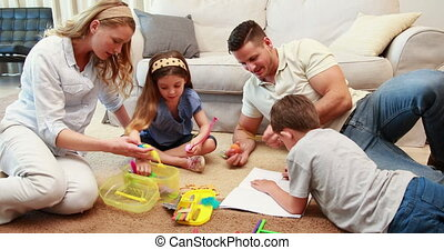 Young siblings doing arts and crafts on the rug with parents...