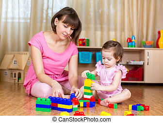 mom and kid girl playing block toys at home
