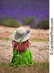 Romantic lady wearing green dress and hat, sitting in front of violet lavender field. Close, back-view. The hat is decorated with lavender twigs.