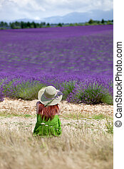 Young brunette female in green dress sitting in front of violet lavender field. Wearing hat decorated with lavender twigs. Back view. Blue sky above.