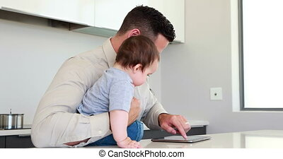 Father holding his baby before work and using tablet at home...