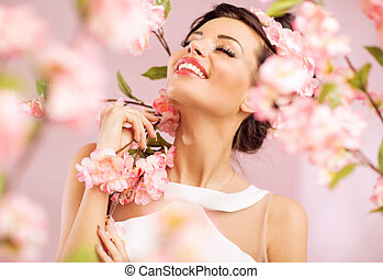 Pleased brunette woman among the flowers