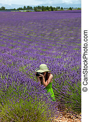 Beautiful female in green dress sitting in lavender field, taking photo of lavender flowers. Placed in foreground, side view. Wearing light green hat, decorated with lavender twigs.