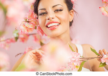 Pretty brunette lady among the flowers