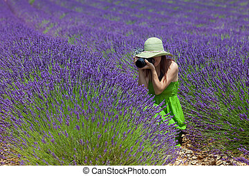 Beautiful woman among lavender photographing some lavender...