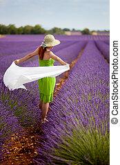 Brunette woman walking in lavender field in Provence, France.
