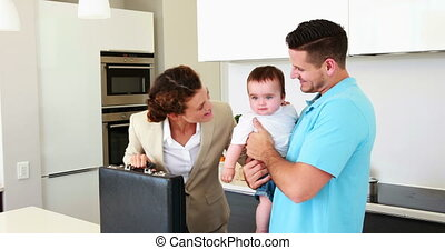 Working mother waving goodbye to house husband and baby at...