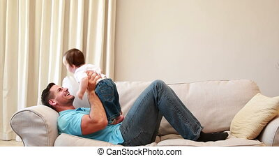 Father playing with his baby boy on the couch at home in the...