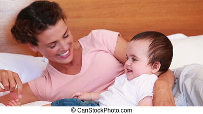 Happy mother tickling baby son on bed at home in bedroom