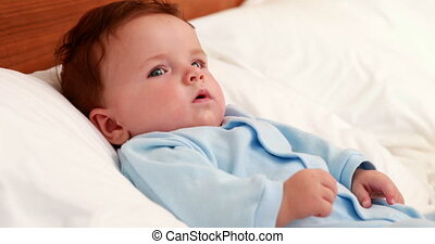 Baby boy in blue babygro lying on bed at home in bedroom