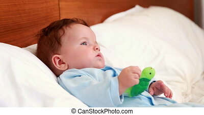 Baby boy in babygro lying on bed at home in bedroom