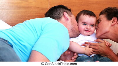 Happy parents kissing their baby son on bed at home in...